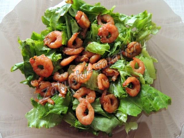 Креветки, выложенные на листья салата
